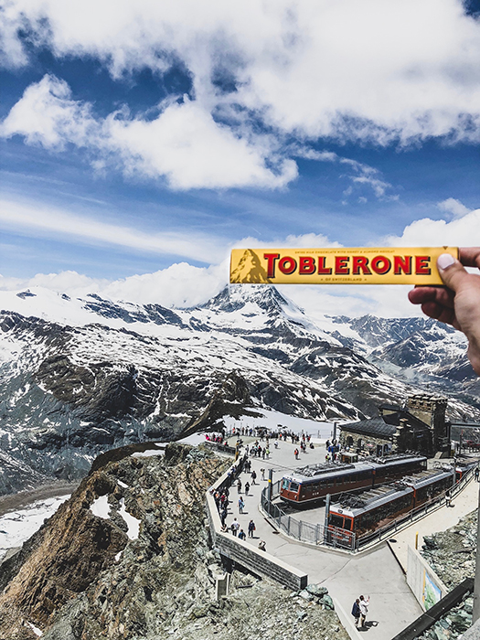A person holding a toblerone chocolate bar over a mountainous landscape