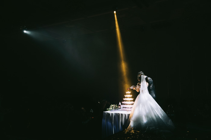 A wedding photography shot of the newlywed couple cutting the cake in low light with a spotlight shining above them - how to fix bad photos