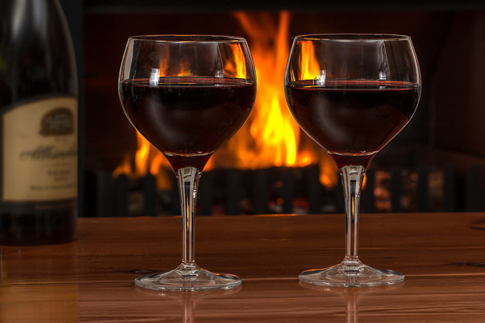 A photo of a bottle of wine and two glasses with a fire in the background, the result of using gaussian blur in photoshop