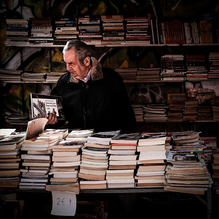 A street portrait of a man browsing books in an outdoor market - gestalt theory photography
