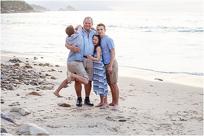 A fun and casual portrait of a family of four posing on the beach - emotional photography