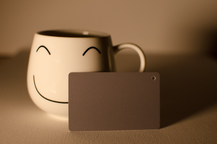 A smily face mug on a neutral background beside a photography grey card for color balance