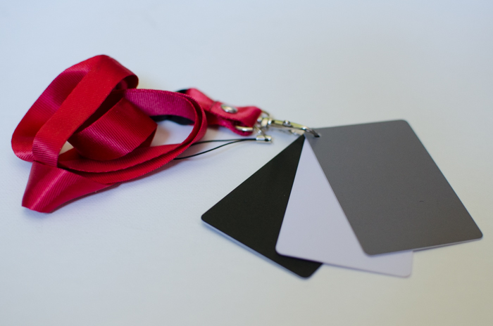 A small set of photography grey cards on a pink ribbon