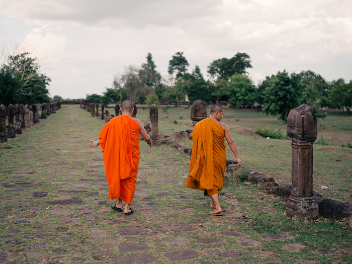 Two Buddhist monks walking through a field