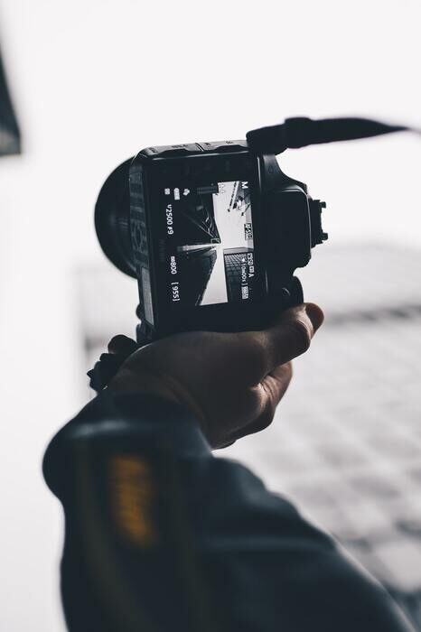 Black and white photo of a camera taking photo of a skyscraper