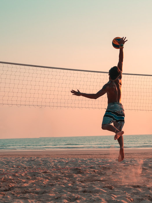 A portrait of a person playing volleyball on the beach at sunset
