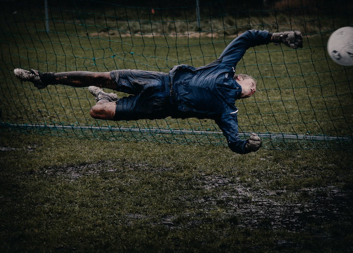 An action shot of a goalkeeper trying to save a ball