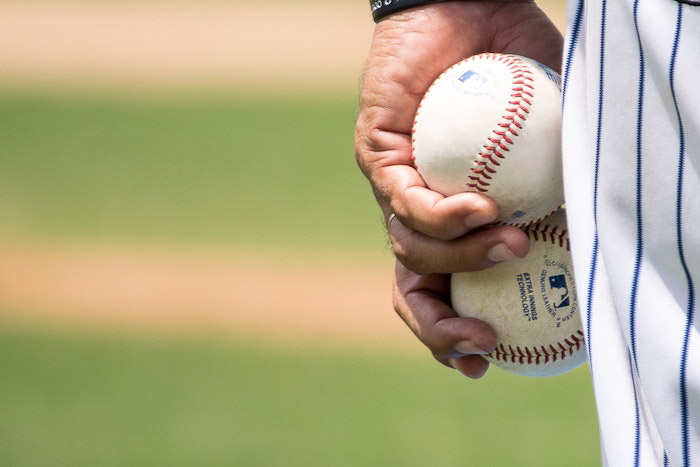 A close up of a baseball player holding two balls