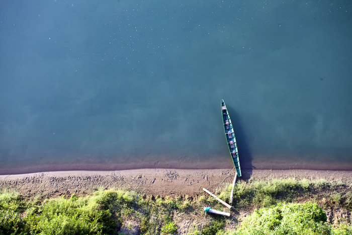 An aerial view of a small boat in a coastal minimal landscape