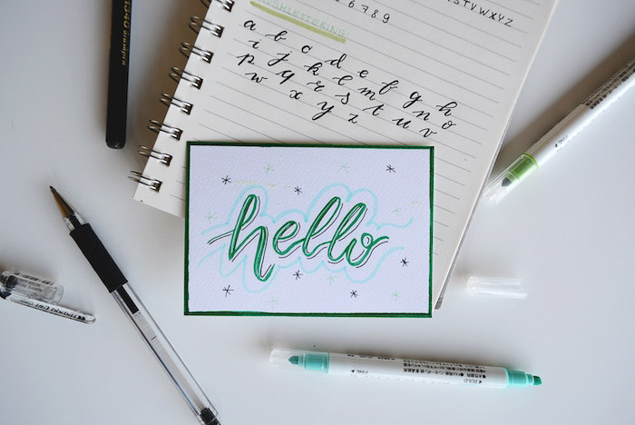 A flat lay of stationary including a notebook with the word 'hello' written on it