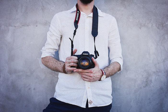 A photographer holding a Canon DSLR camera - photography branding