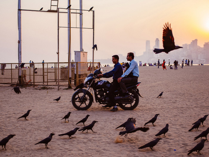 A photo of people on motorbikes on a beach in Bombay - How to Use Smart Objects in Photoshop