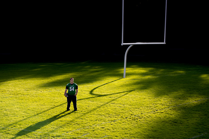 A rugby player standing on a sportfield shot with dramatic shadows