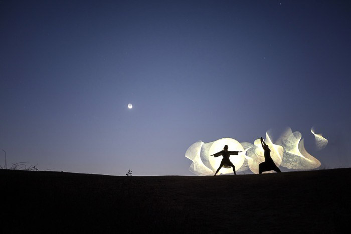 The silhouettes of two people doing creative light painting - slow shutter speed photos