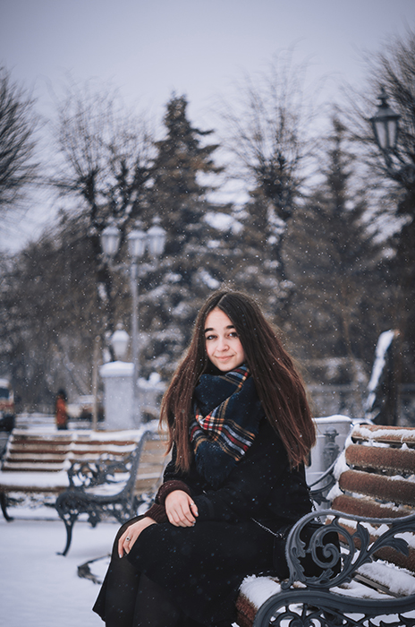Atmospheric winter portrait of a female model posing on a bench in the falling snow