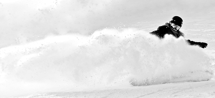 Atmospheric sports photography shot of a female snowboarder posing in action - winter portrait photography