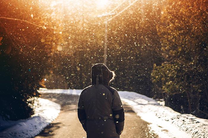 Atmospher winter portrait of a model walking down a road under falling snow