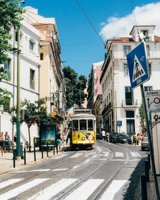A street photography shot of a tram running between buildings on a clear day, shot using a standard lens