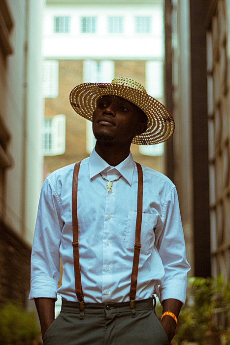 An outdoor model of a male model in a straw hat, shot using a standard lens