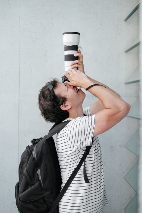 A portrait of a photographer shooting upwards with a telephoto lens