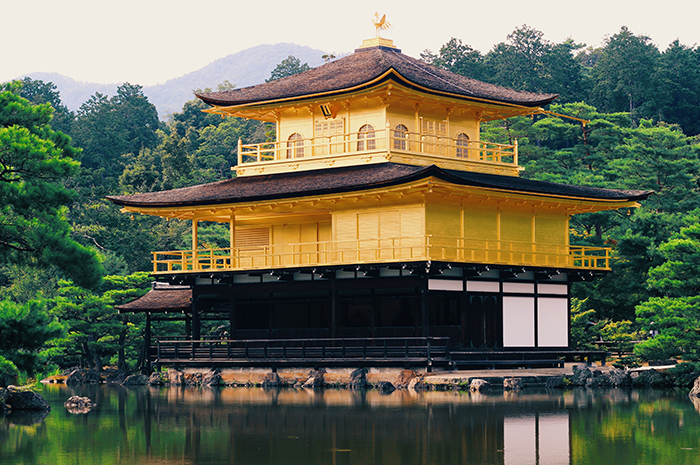 The gold covered temple of Kinkakuji in Kyoto,next to a forest and a pond. Japan photography tips