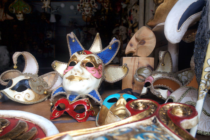 A collection of Venetian festival masks in a store window - best tips for Venice photography