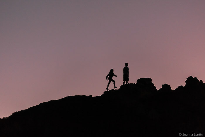The silhouettes of two photographers walking through a landscape in low light - best wildlife clothes