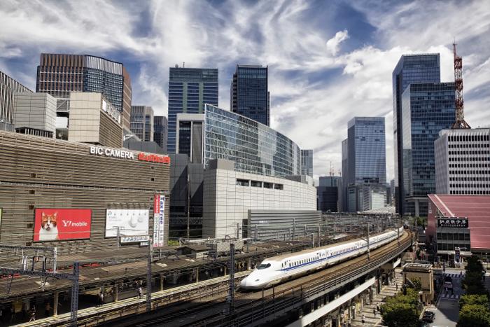 A modern ttrain moving through a large city