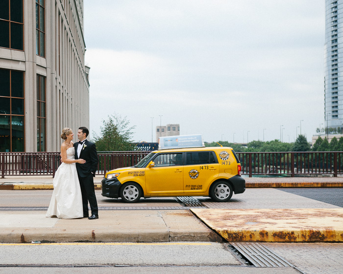 A newlywed couple posing beside the yellow cab of Downtown Chicago - capturing the decisive moment in photography