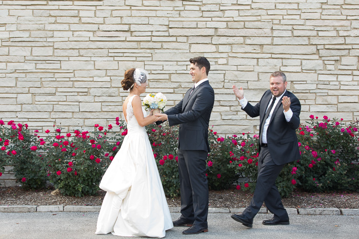 Humorous portrait of a newlywed couple was having their first look with the best man rushing in to goof it up for them - the decisive moment in photography