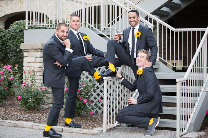 A fun casual wedding portrait of a group of groomsmen hanging out and enjoying themselves.