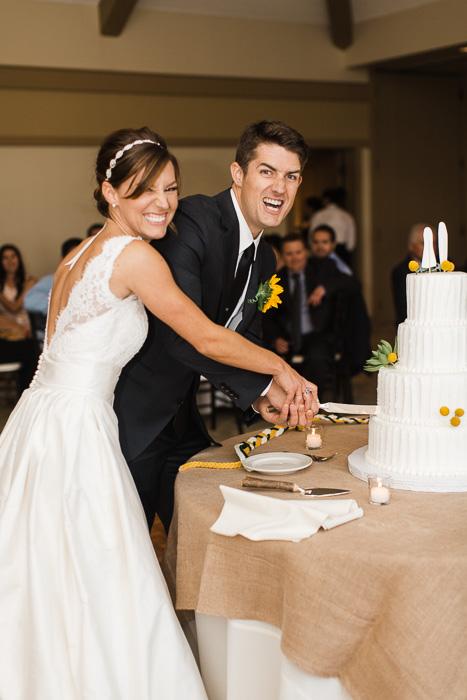 Fun wedding porttrait of the newlyweds cutting the cake