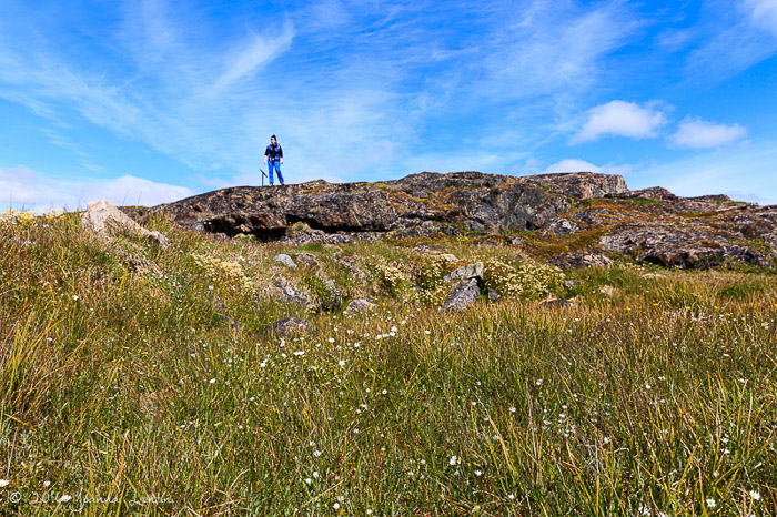 A female photographer standing on a rock on a clear day - adventure photography gear