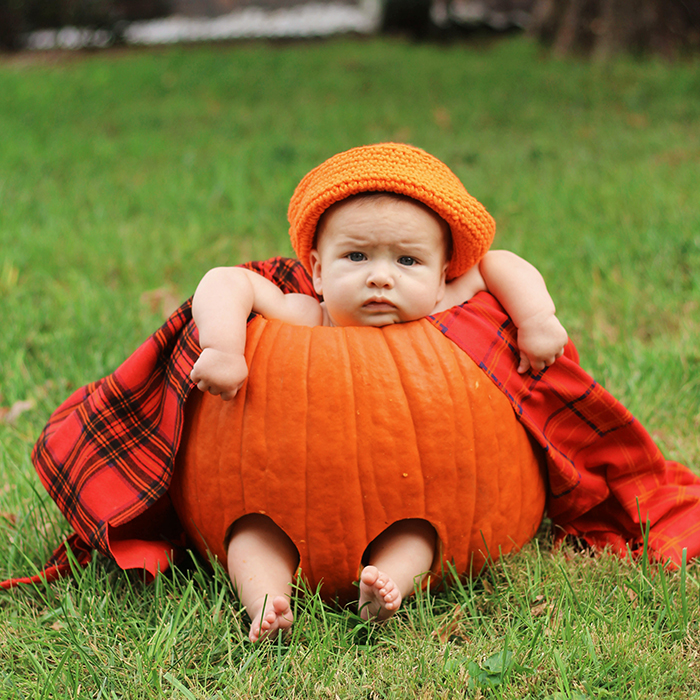 Adorable outdoor portrait photos of a baby in a pumpkin