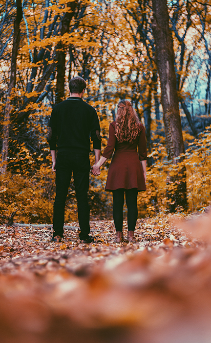 Autumn portrait of a couple holding hands in a forest