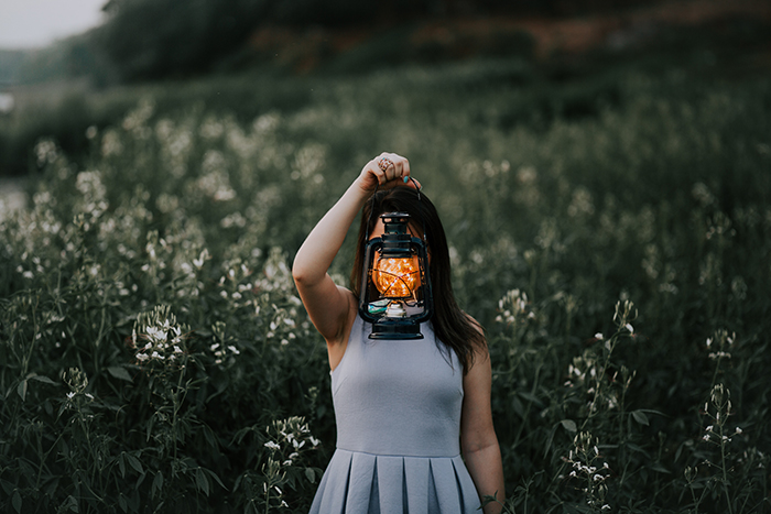 An outdoor portarit of a female model holding a lantern in front of her face - fall photography tips
