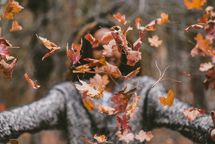 Beautiful autumn photography of falling leaves in the foreground of a female model