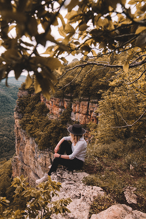 An outdoor portrait of a female model sitting on rocks amidst a beautiful mountainous landscape - fall photography tips
