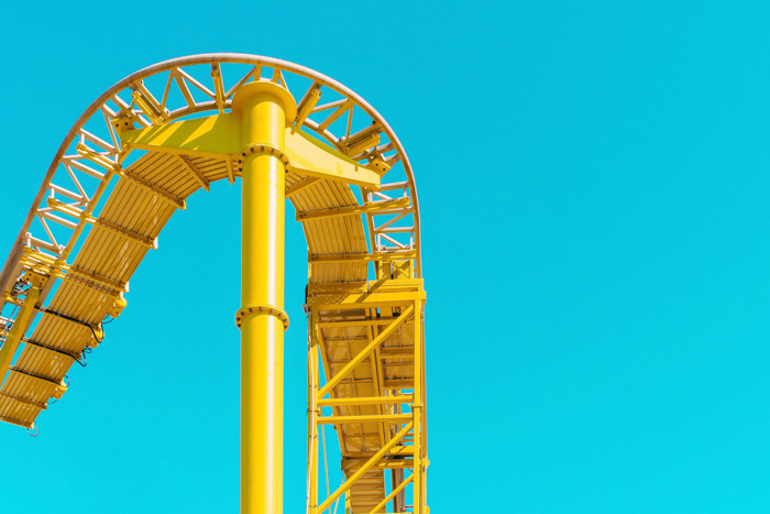 A yellow roller coaster rail enters and leaves a blue background frame - complementary colors