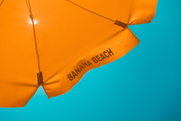 An orange parasol sits in front of a inviting blue sky
