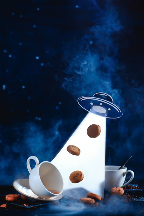 An outer space themed food still life including coffee cups, sugar ,cookies and a flying saucer