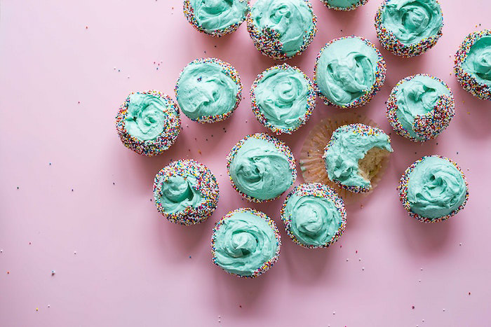 Overhead shot of a plate of green frosted cakes against a light background