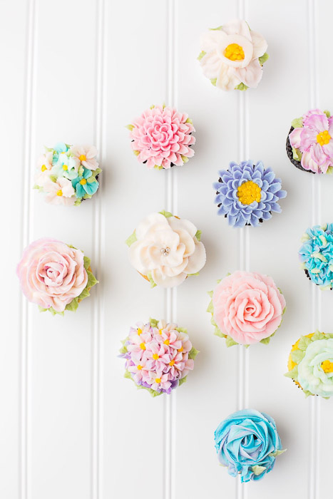 Overhead shot of flowery frosted cakes against a light background