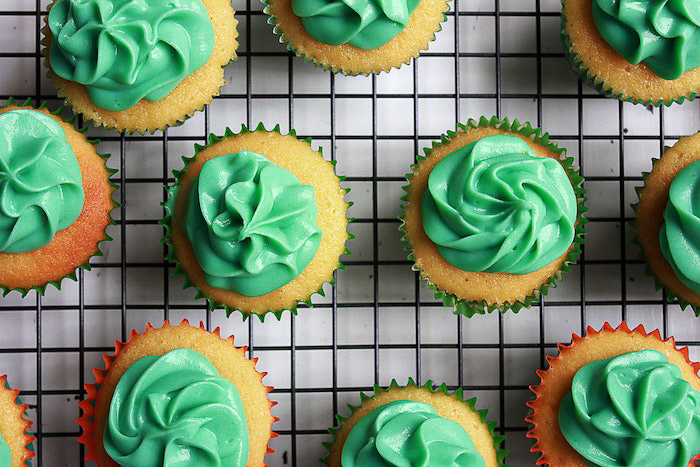 Overhead cup cake photo of a plate of green frosted cakes on a wire rack