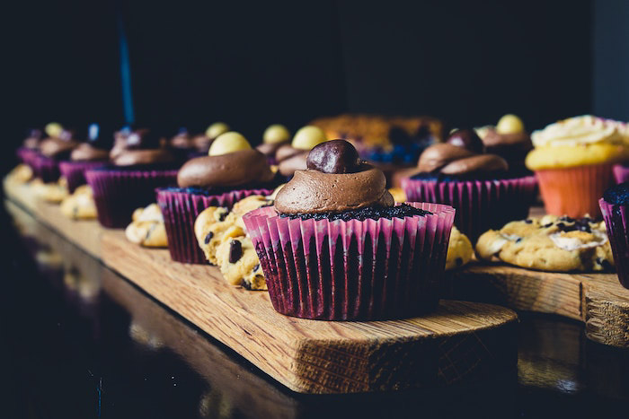 Atmospheric shot of cookies and cupcakes against a dark background