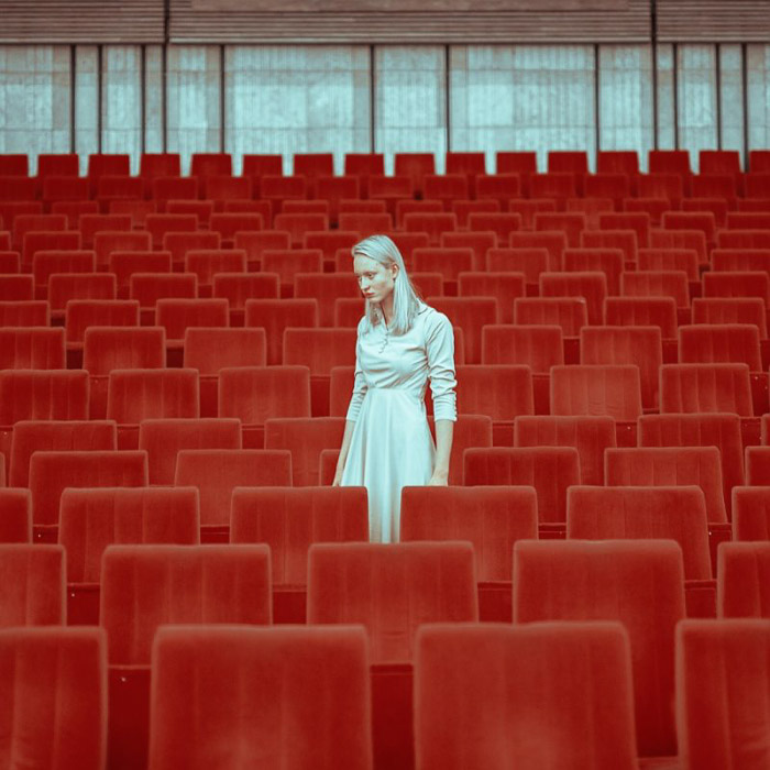 A femal model in white posing between red theatre seats by v - fashion photography style