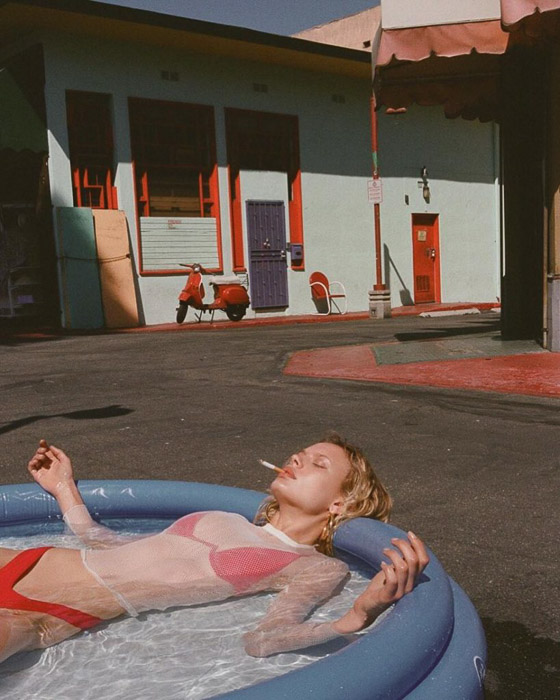 A blonde fashion model in a plastic swimming pool smoking a cigarette by v - fashion photography inspiration