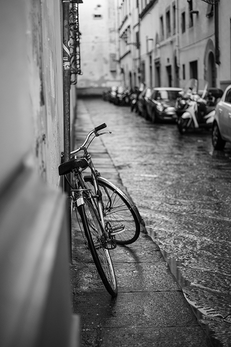 A street photo of a bicycle leaning against a wall