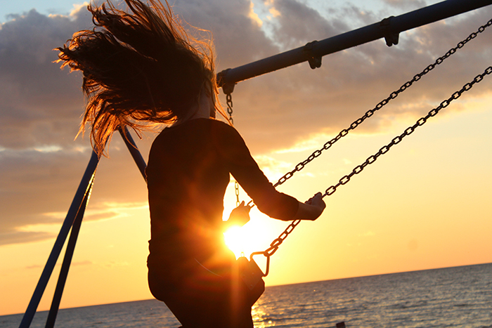 Atmospheric portrait of a girl swinging on a swing set at sunset - form in photography