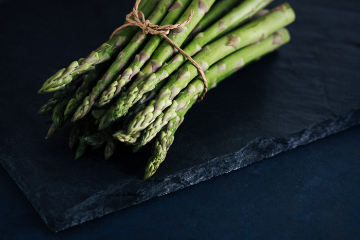 Atmospheric food photo of asparagus on dark background
